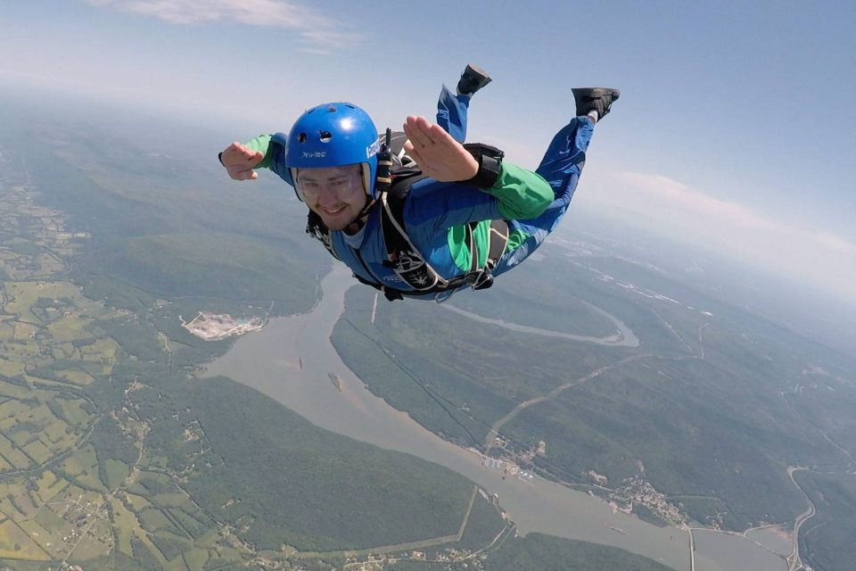 Man in green skydiving gear smiles during AFF training at the Skydive Company