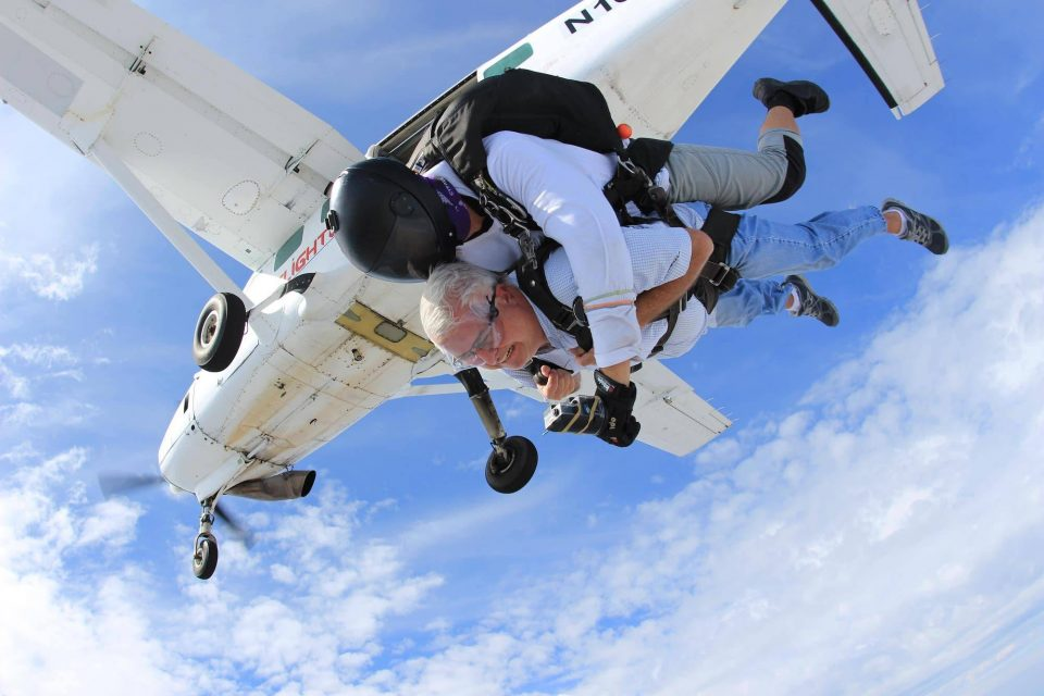 Older gentlemen enjoying the rush of free fall after leaping from the skydiving company aircraft
