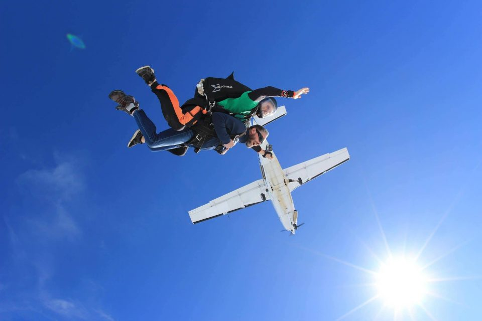 Male tandem skydiver enjoys the beautiful blue skies after leaping into free fall