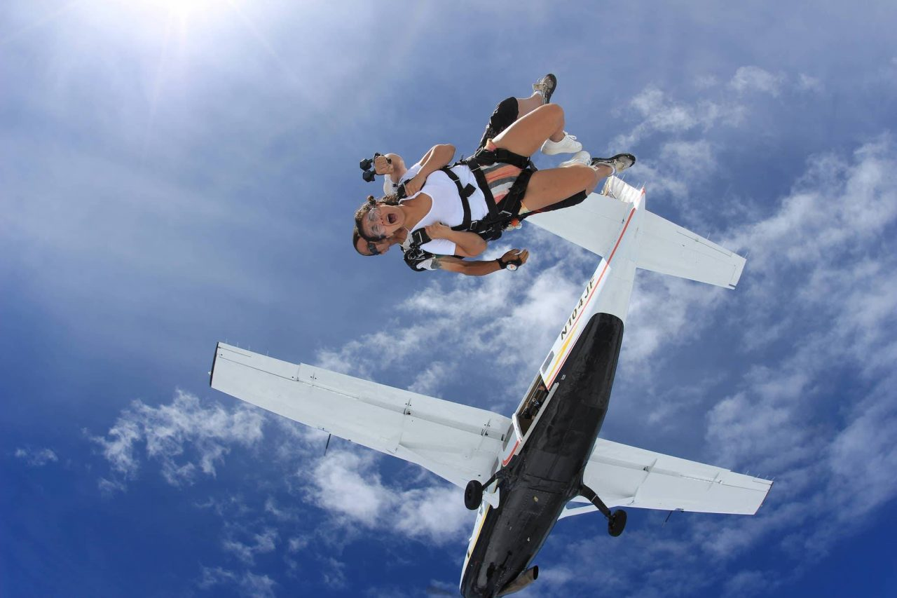Female wearing shorts and white shirt takes the leap from the skydiving company airplane into free fall