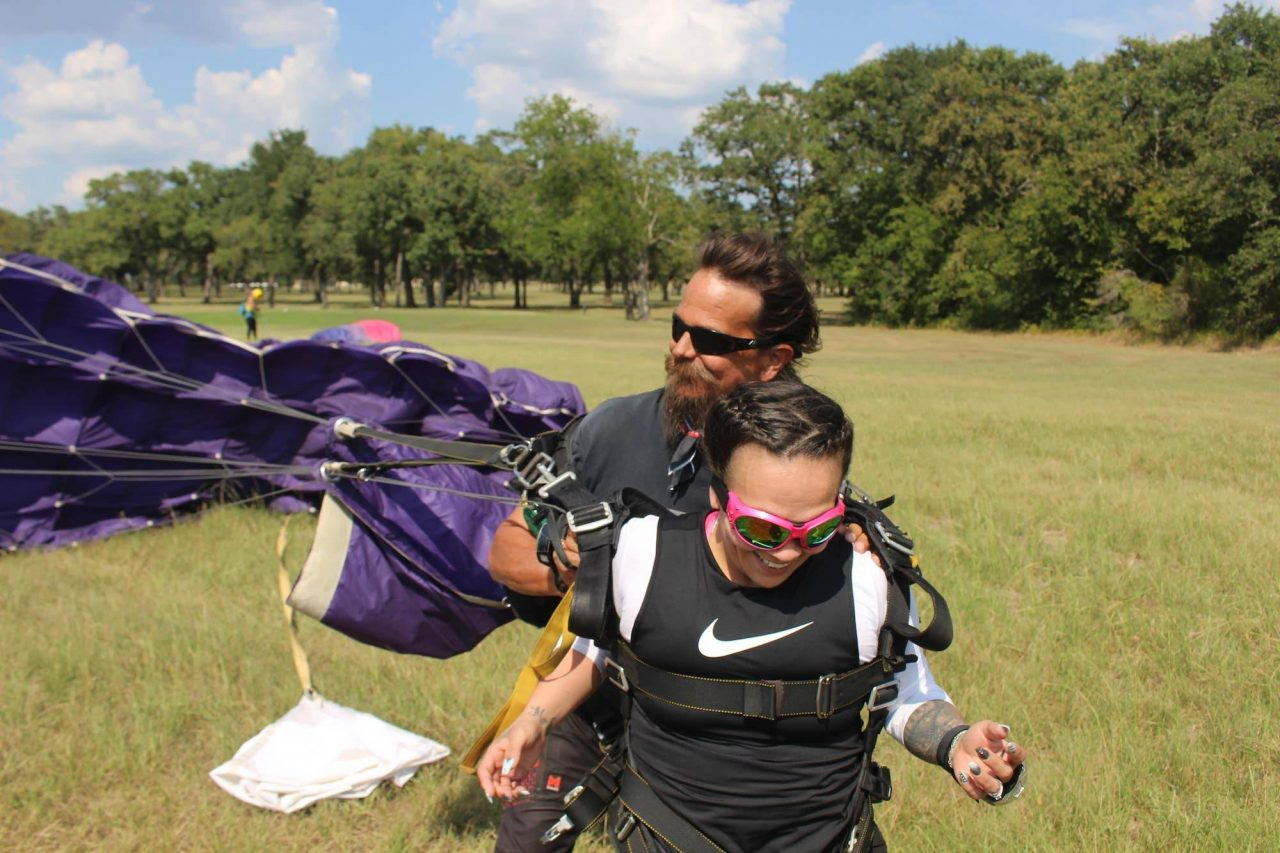 Women comes in for landing with tandem instructor after an awesome skydive at the skydiving company in texas