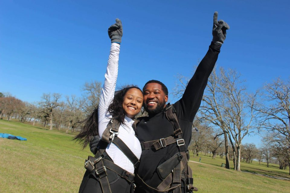 Couple stands together with hands pointed towards the sky after an awesome skydive at the skydiving company in texas