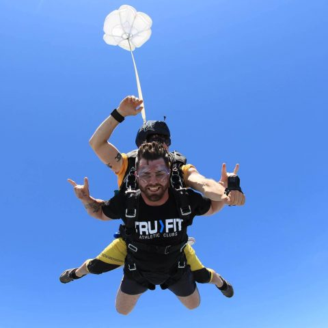 Man wearing a true fit shirt smiles during free fall portion of his skydive