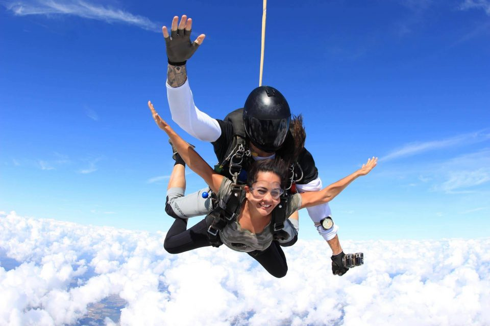 Women in camo shirt smiles during free fall portion of her skydive