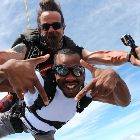 Man wearing white shirt and dark skydiving googles smiles while enjoying his tandem skydive at the skydiving company in texas
