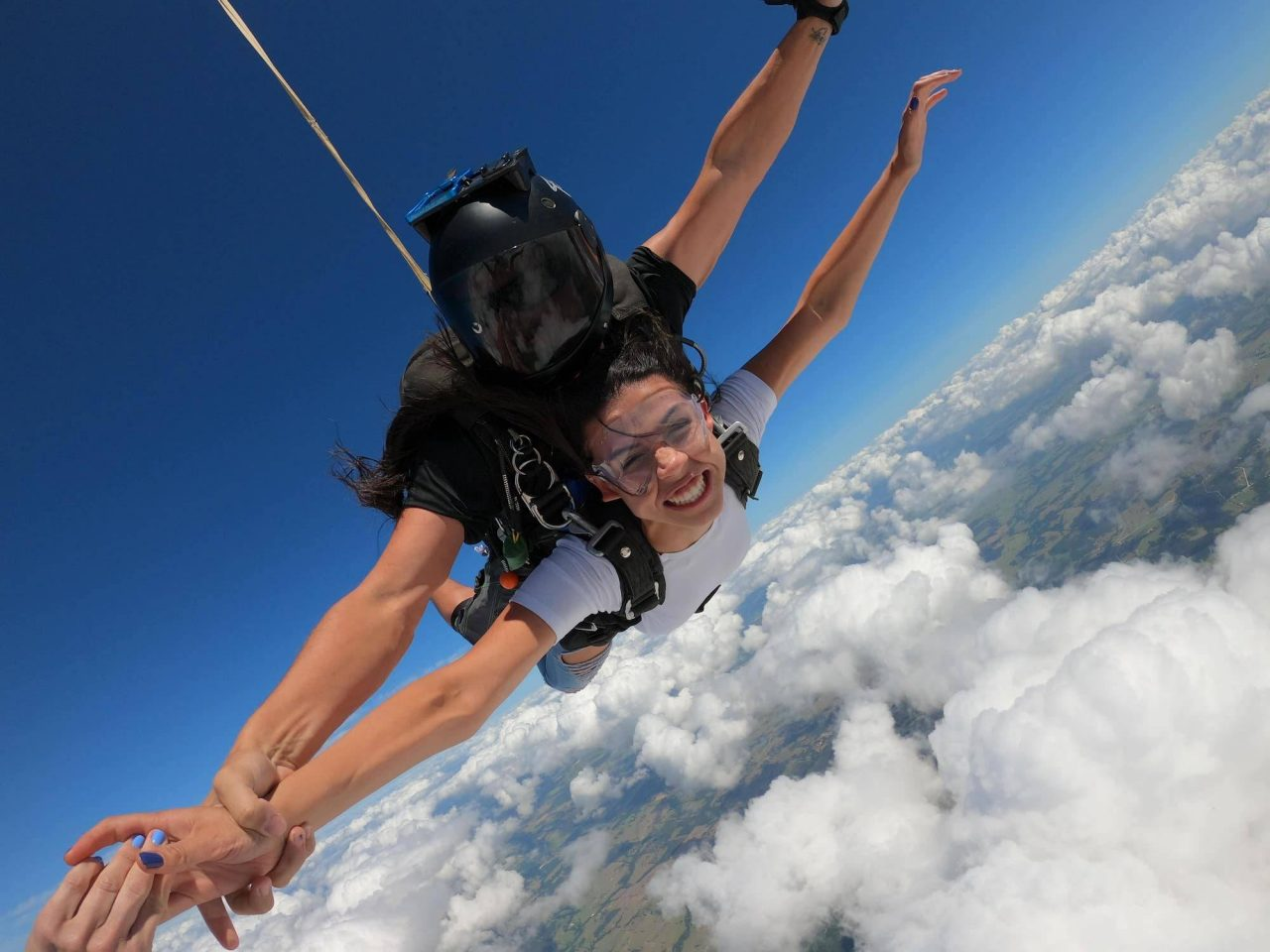 Women wearing white shirt smiles and touches hand with a fellow skydiver during free fall
