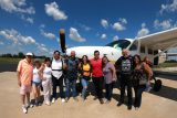 Family members gather around with tandem skydivers in front of the skydiving company aircraft