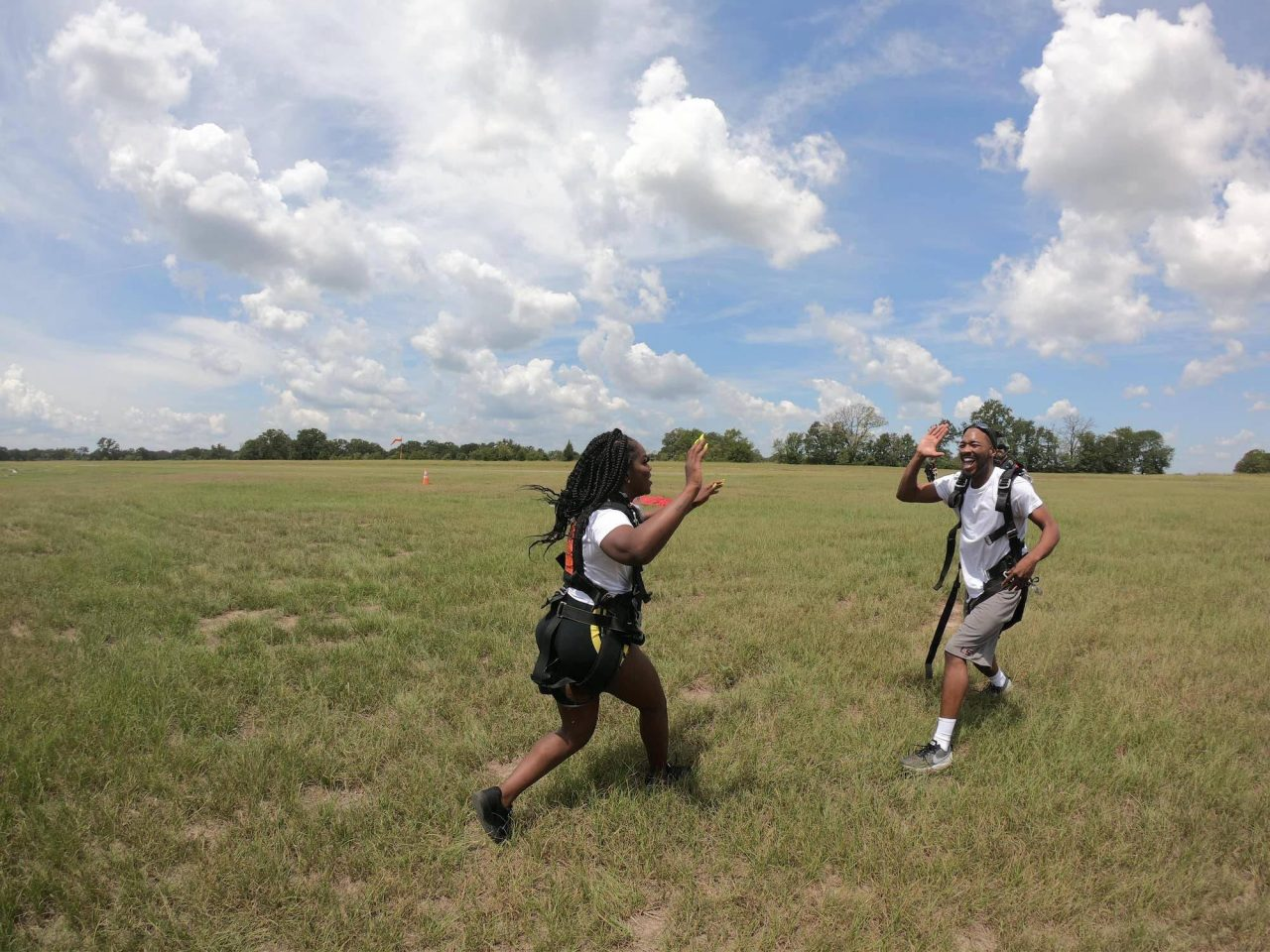 Man and women run towards each other for a high-five after an awesome skydive with the skydiving company