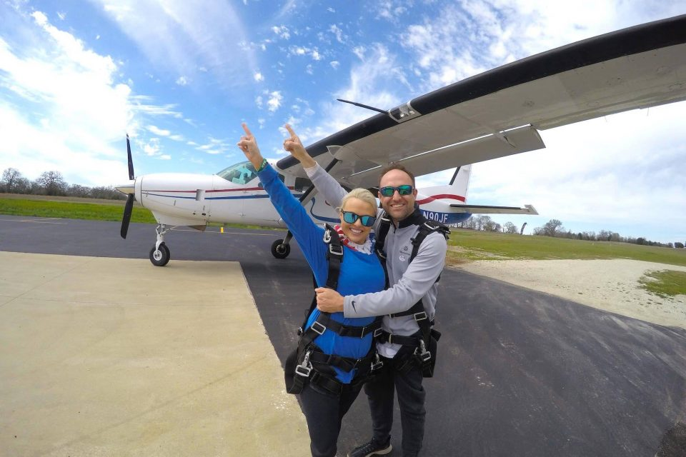 Two tandem jumpers hugging before going up in the skydiving company airplane for a skydive