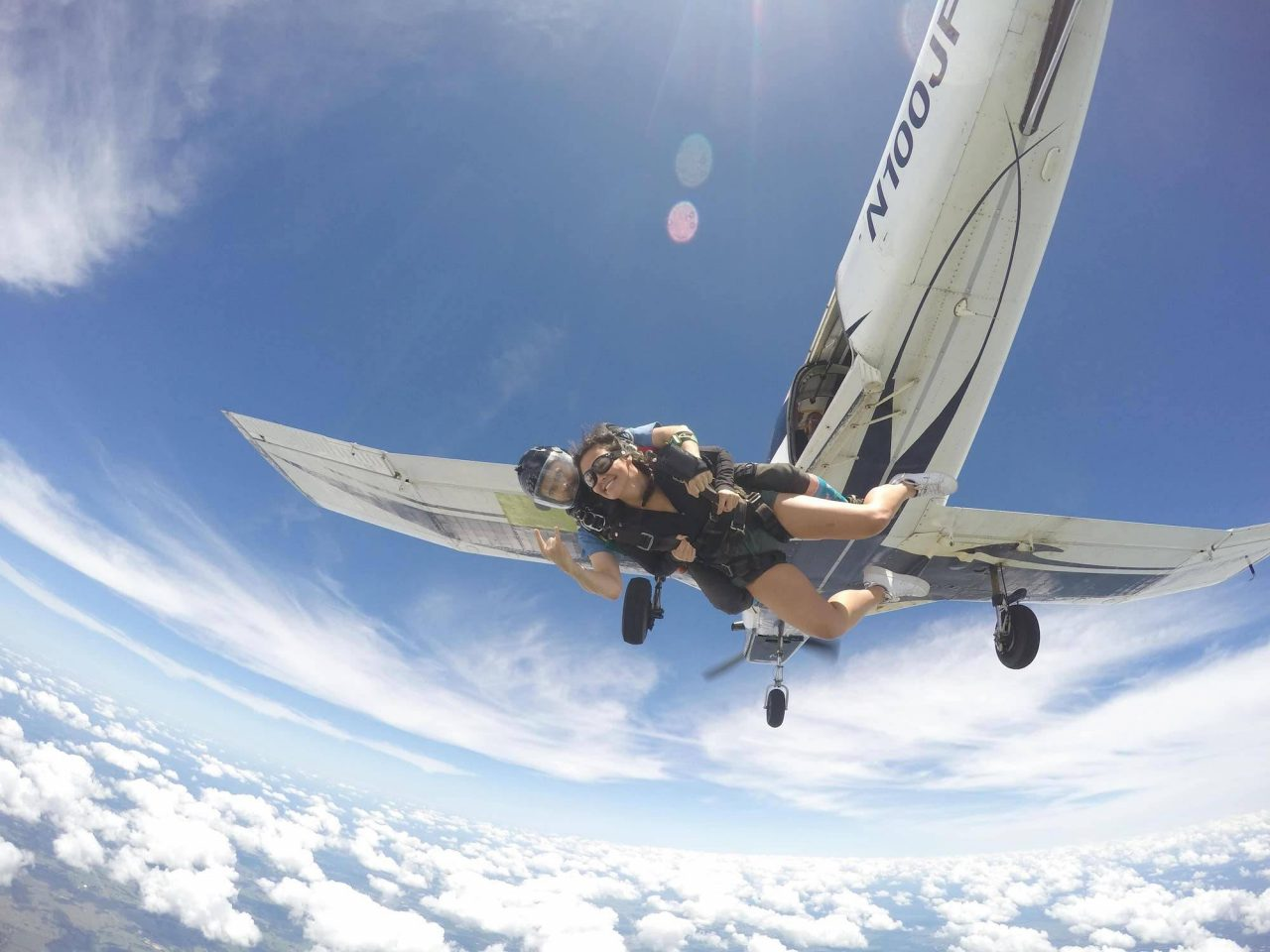 female wearing a black jacket and skydiving googles takes the leap from a the skydiving company airplane into free fall