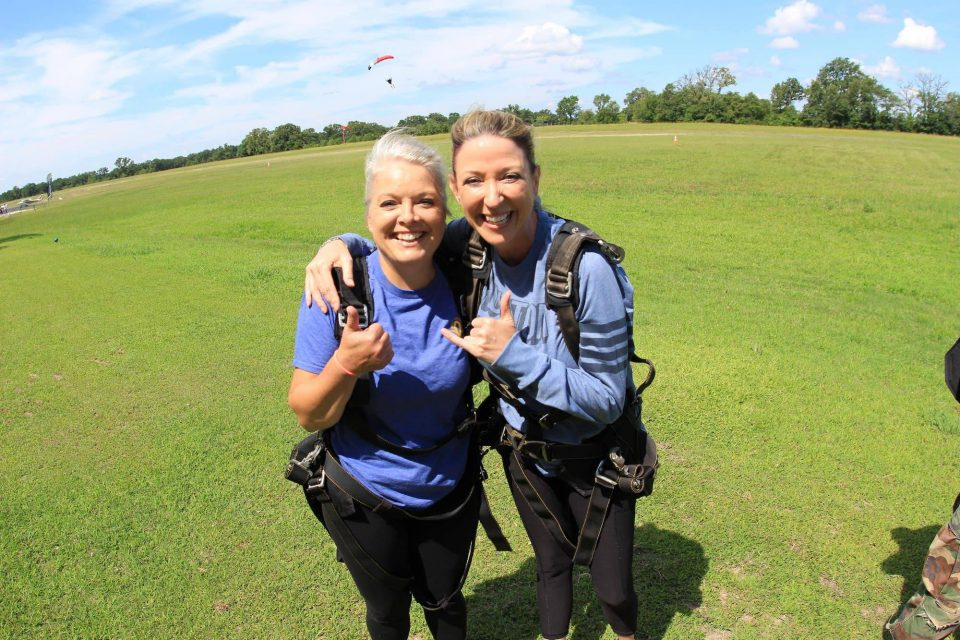 Two women celebrate on the ground after an awesome skydive at the skydiving company