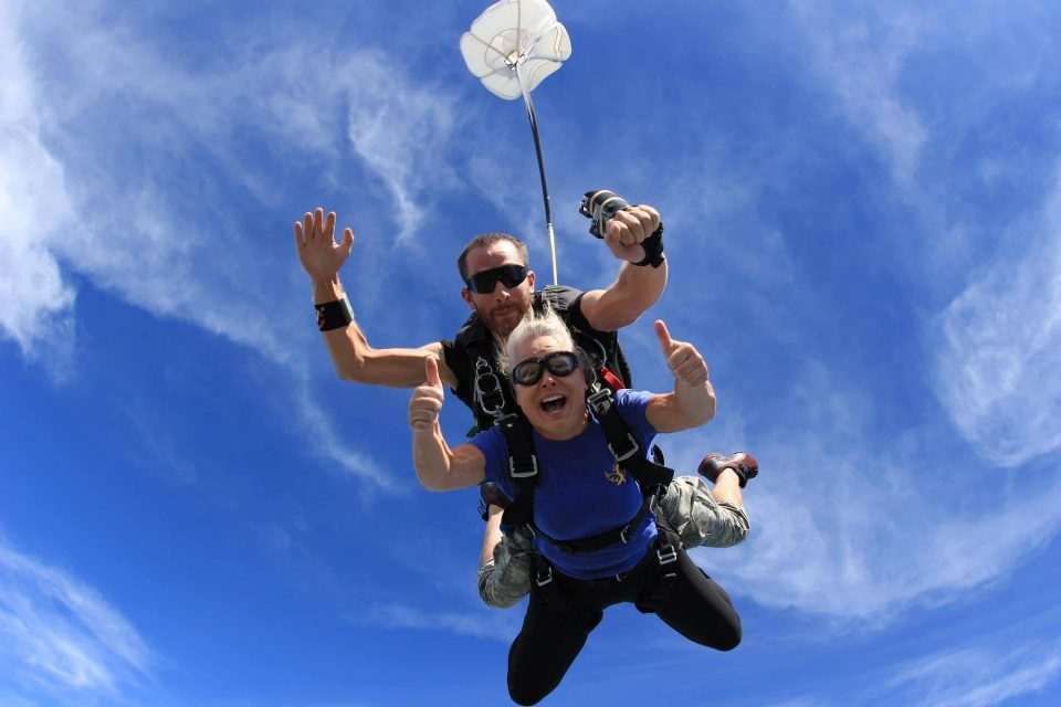 Women in blue shirt gives two thumps up during an awesome skydive at the skydiving company