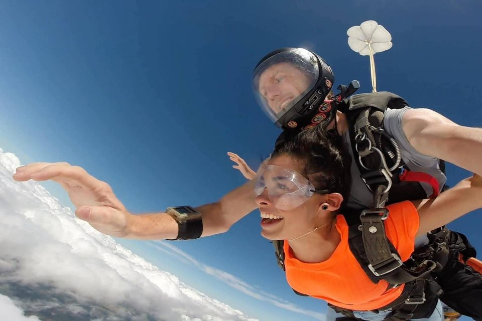 Women wearing an orange shirt and clear skydiving googles enjoys free fall with a The Skydiving Company tandem instructor