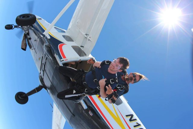 Man in blue shirt takes the jump for a the skydiving company aircraft into free fall on a beautiful sunny day