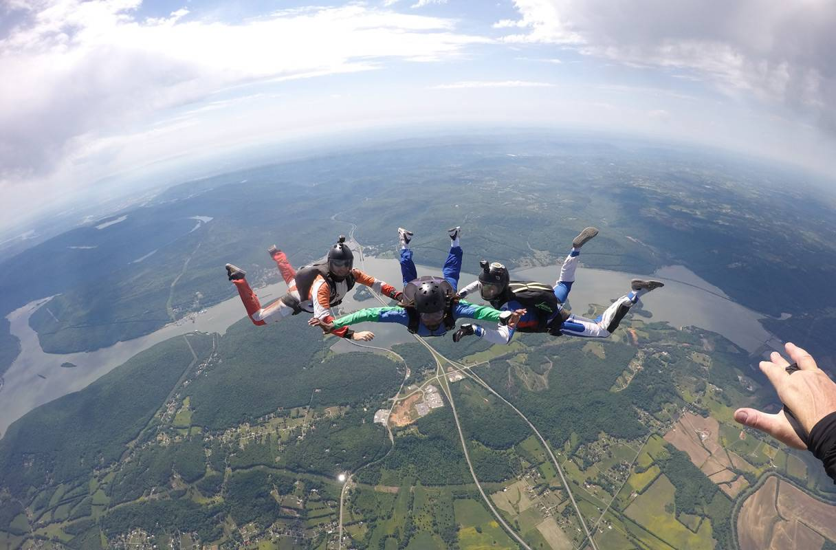 AFF student practicing flying positions during his skydive with two instructors at the skydiving company