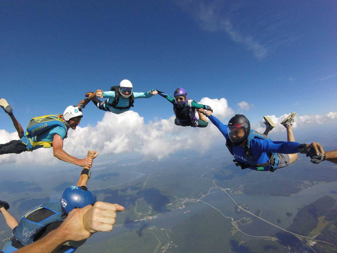 Group of experienced skydivers link arms in circle formation during their skydive