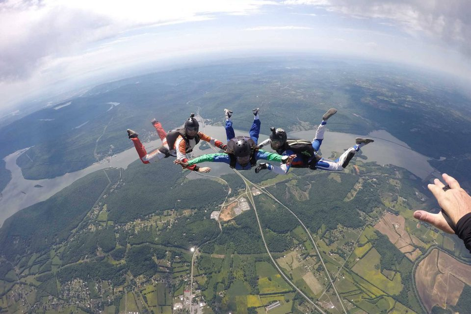 AFF student practices flying position during class with two instructors from the skydiving company in texas