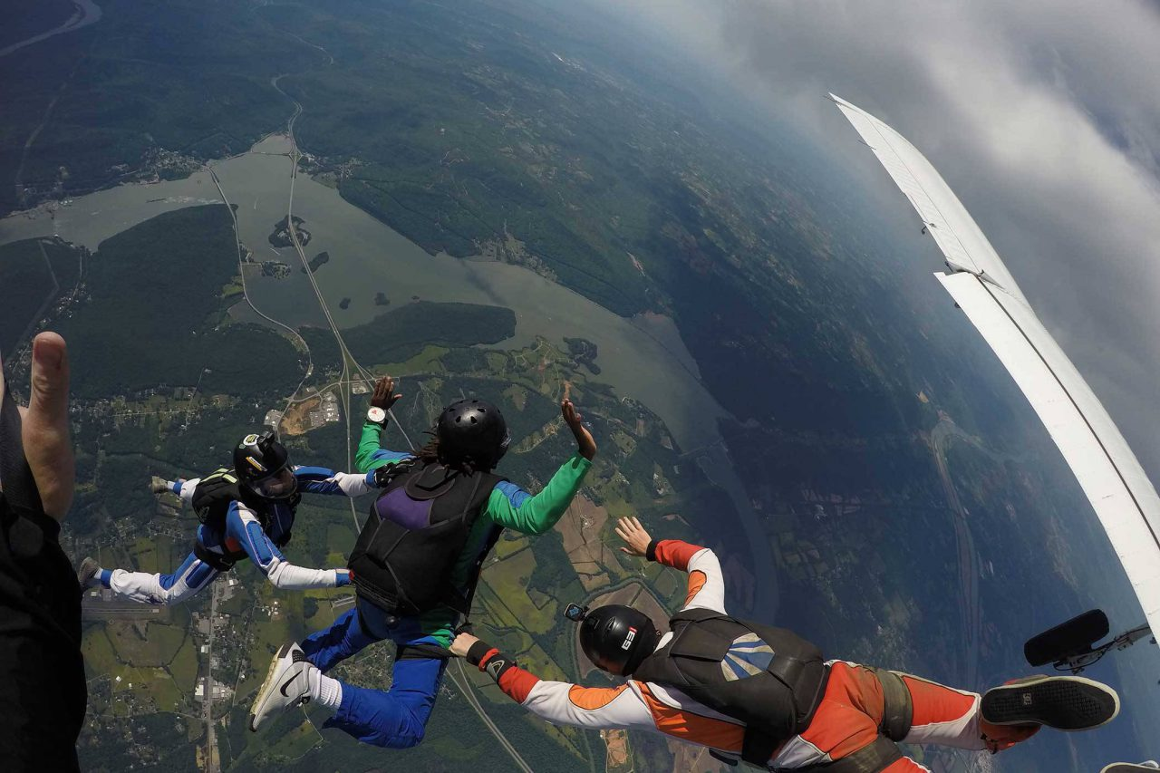 AFF student wearing green and blue skydiving gear practices the free fall portion of his skydive with instructors