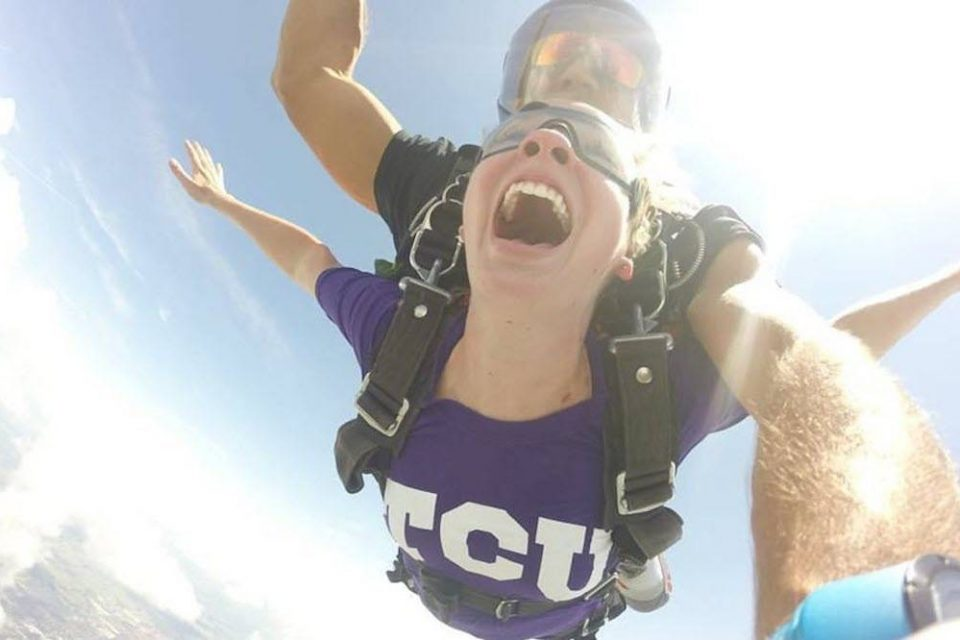 College student wearing a purple shirt enjoys her skydive at the skydiving company in texas