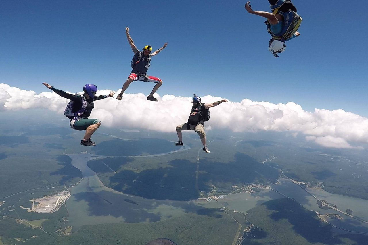 Experienced jumpers in the sitting position during a skydive