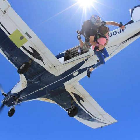 Female tandem skydiver wearing pink shirt jumps from airplane into free fall