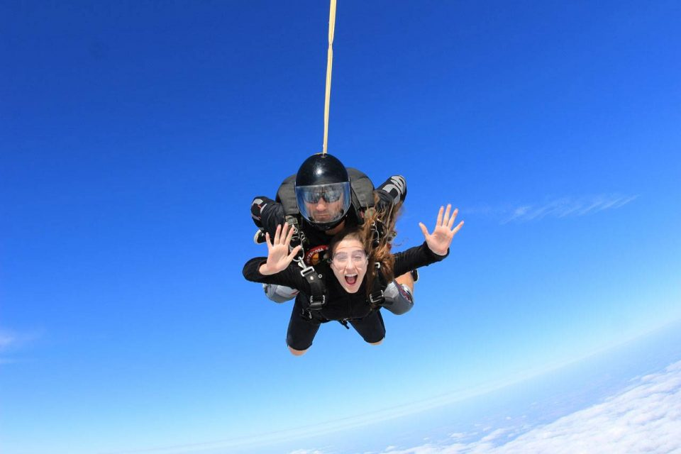 Women in black shirt smiles with arms out during an amazing skydive at the skydiving company