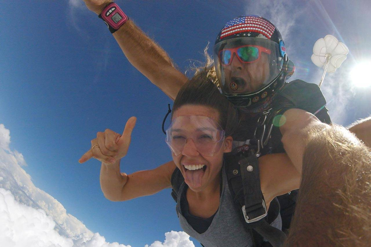Women in gray shirt smiles with tongue out while in free fall with the skydiving company tandem instructor