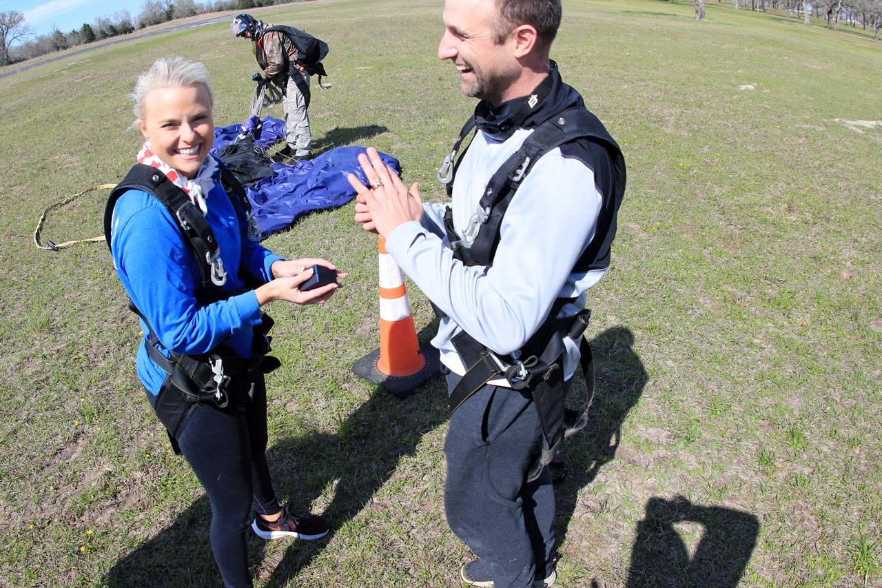 Man and women stand together in celebration after experiencing an amazing skydive at The Skydiving Company