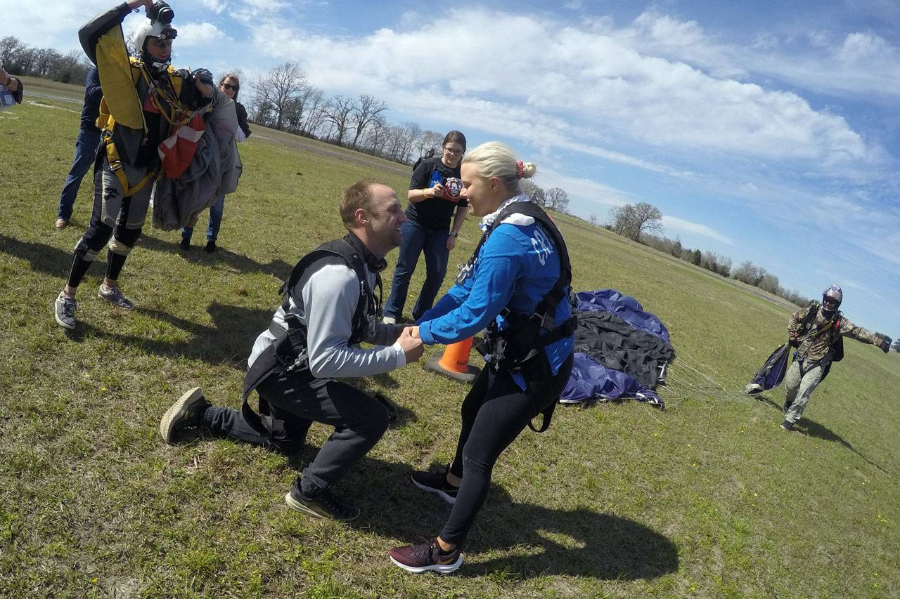 Women in blue shirt smiling at man who is proposing to her after landing from a tandem skydive at the skydiving company